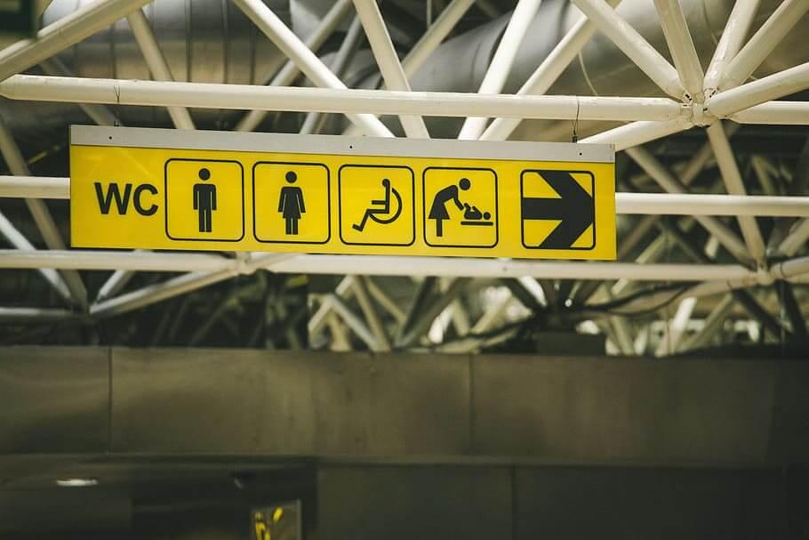 Skylt på offentlig plats som visar vägen till toalett med skötbord